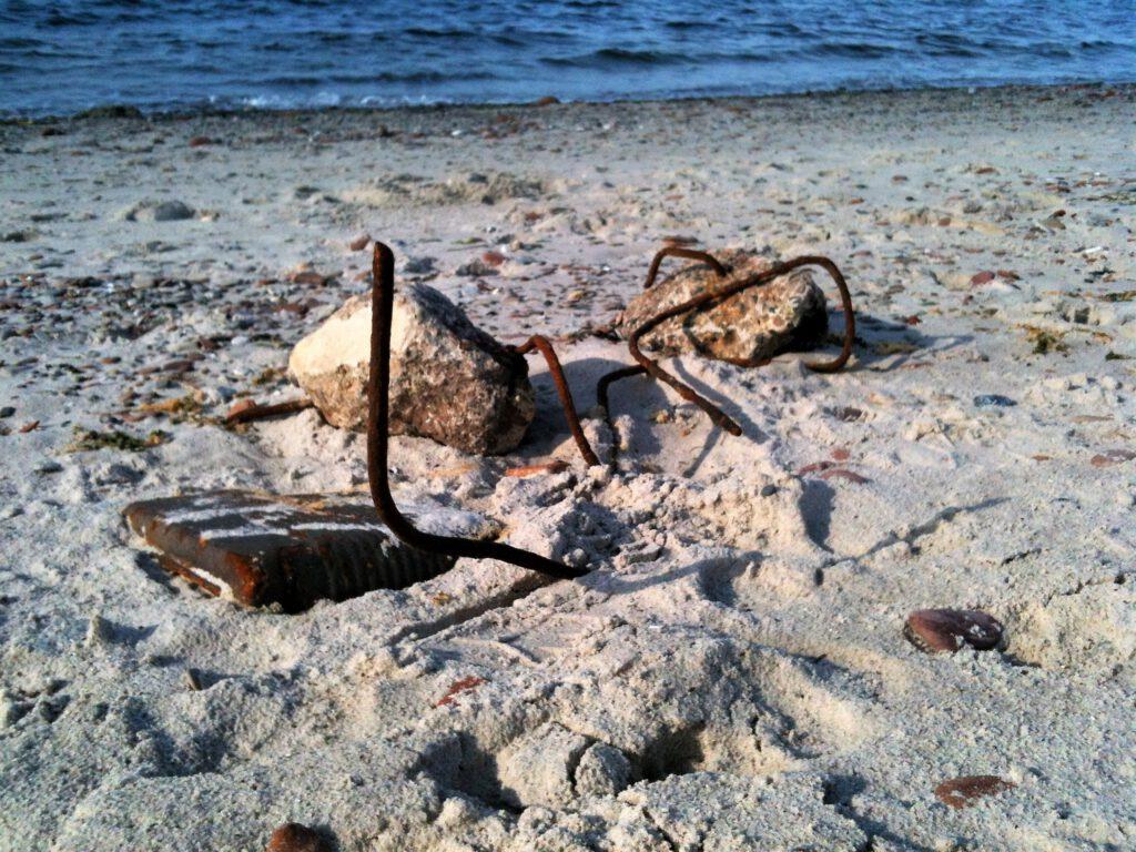 Fundstücke am Strand mit Steinen und Draht