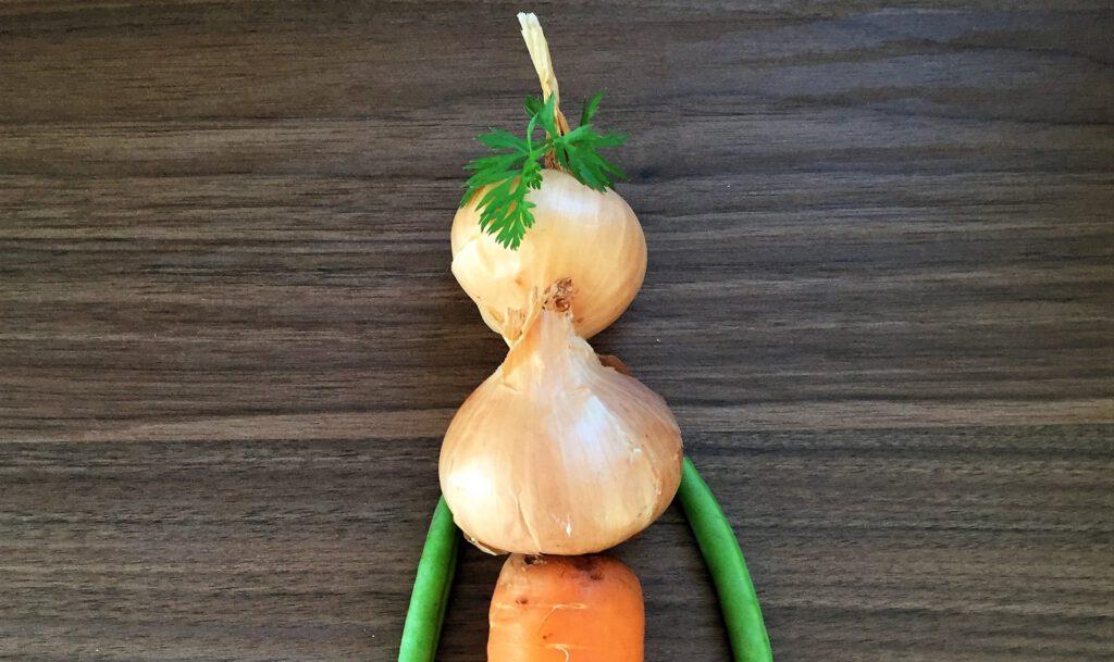 Figur aus Zwiebeln als Körper, Bohnen als Arme und Karotte als Beine